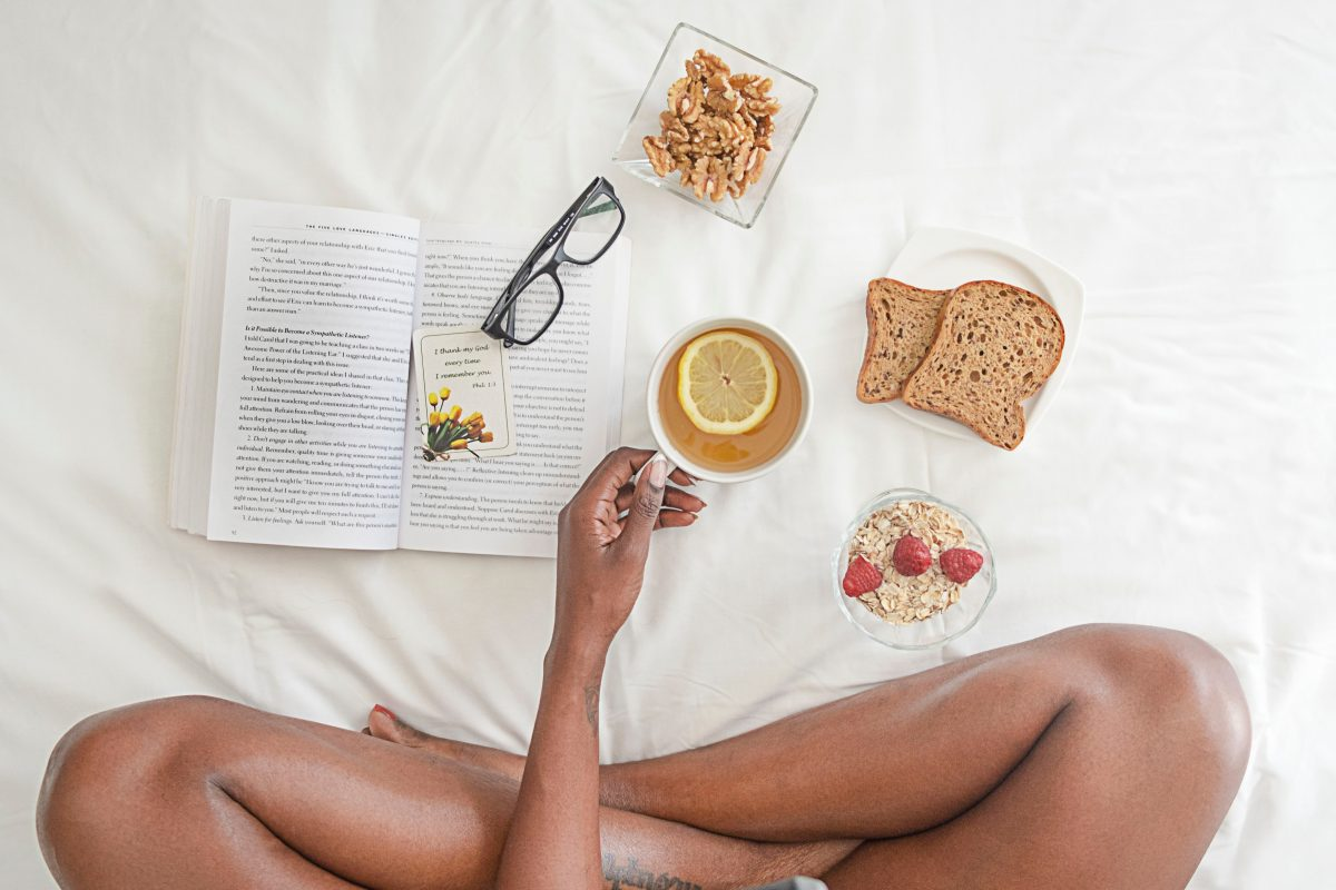 Kendra Nix Black-woman-holding-white-ceramic-mug-with-lemon-near-book